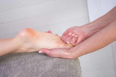 beauty center: Close-up of female hands doing foot massage at beauty center