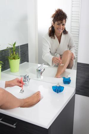bra and panties: Close up of woman shaving legs in bathroom