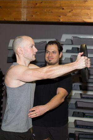 arm muscles: Man exercising his arm muscles by lifting dumbell in a fitness club.
