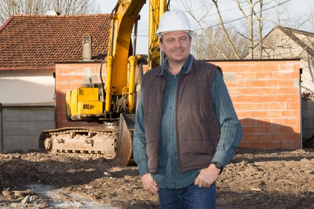 service engineer: Smiling Engineer  at construction site with blue sky background. Stock Photo