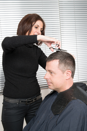 coiffeur: Female hairdresser cutting hair of smiling man client at beauty parlour