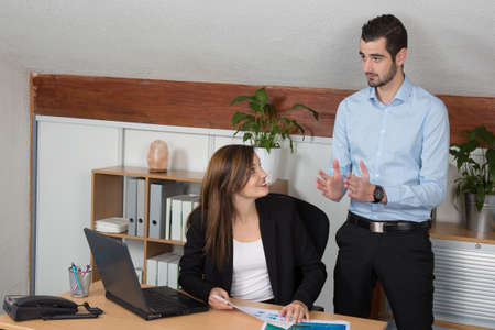 outgoings: Business meeting: professional successful team; man and woman talking together in front of pc. Stock Photo