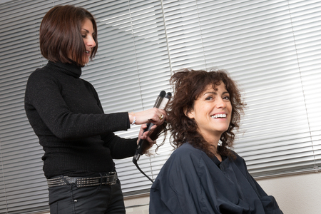 hair stylist: Stylist curling hair for woman. Girl care about her hairstyle
