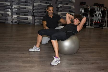 fit ball: Personal trainer assisting senior woman doing fit ball exercise at home, smiling.? Stock Photo