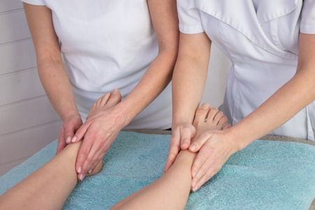 Foot massage with four hands  in the spa room at beauty center