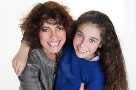 love hug: Close up of a girl and her mother smiling at the camera