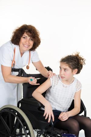 paraplegico: Niña sonriente sentado en la silla de ruedas con el apoyo de un médico en el hospital Foto de archivo