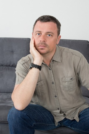 his: Confused man scratching his chin on his couch at home Stock Photo