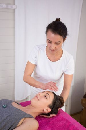 spirit healer: Alternative traditional medicine and massage, young spirit healer doing reiki treatment to old woman. Head and shoulders