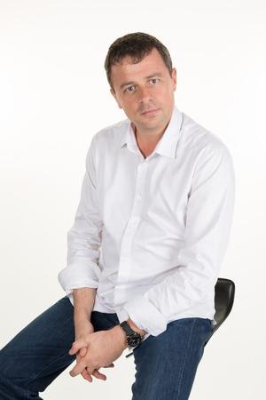 hombres guapos: Hombre joven orgulloso y satisfecho sentado en la silla y mirando a c�mara aislada sobre fondo blanco Foto de archivo
