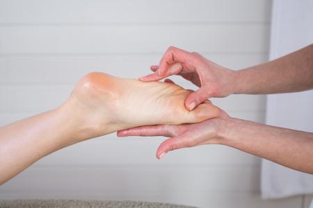 reflexologie plantaire: La femme jouit d'un massage pied dans la création d'un spa (près sur pieds) Banque d'images