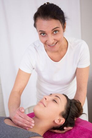 reiki: Happy woman having a reiki treatment in therapy room Stock Photo