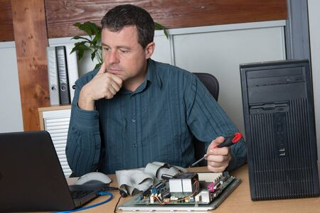 computer tech: Cheerful Technician fixing the computer hardware at office