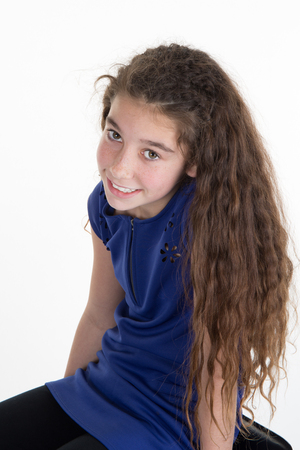 looking directly at camera: Young girl looking directly to the camera with long curly hair.