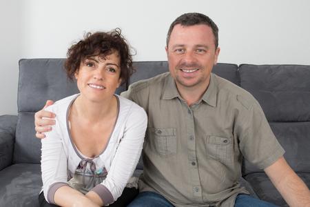 donna innamorata: Coppia felice di relax sul loro divano sorridere alla telecamera a casa in salotto