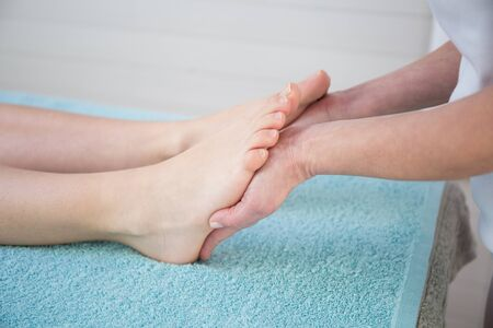 chiropractic: Osteopath doing reflexology massage on female foot against colorful background.