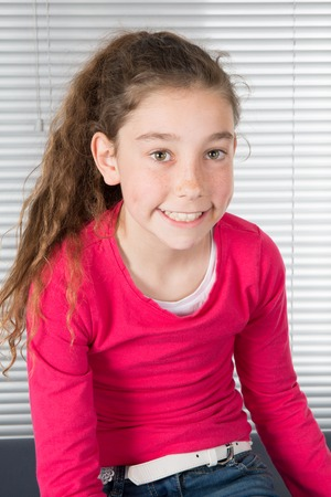 Young brunette girl smiling at viewer under grey background Stock Photo