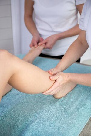 four hands: Four hands doing a  massage to a female foot at beauty center