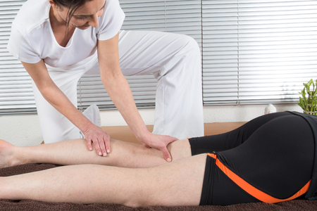 hamstrings: Macro close up of Osteopathic hamstring massage.Therapist applying pressure with hands on back go female leg. Stock Photo