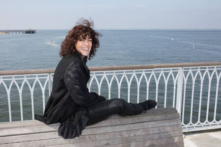 feeling good: Portrait of the  brunette woman at the windy autumn day relaxing on coast feeling good