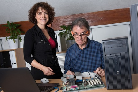 data processor: a male and female technician repairing a computer at office