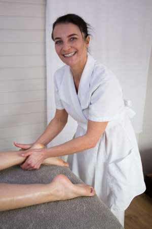 female soles: Smiling caucasian pedicurist working with client at spa. Foot care concept. Stock Photo