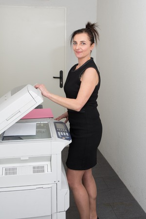 photocopy: Pretty  secretary using  photocopy machine in office Stock Photo
