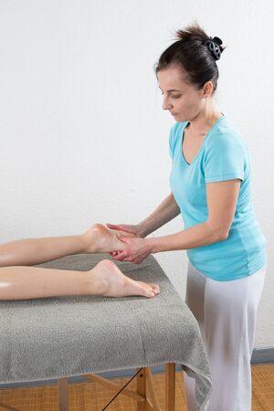 Osteopath doing reflexology massage on female foot against white background.