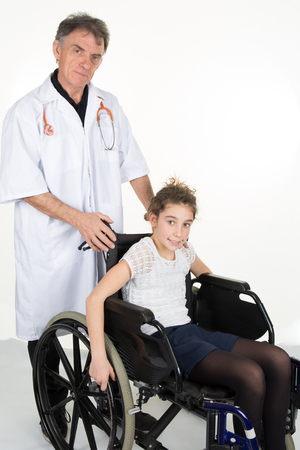 paraplegic: Retrato de una niña sentada en la silla de ruedas con el apoyo de un doctor en el hospital