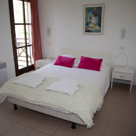 bedchamber: Double Bed In The Bedroom With Desk Lamp Near It