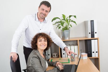 workteam: Workteam in office working on laptop computer Stock Photo