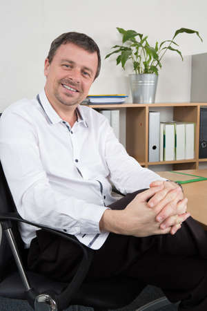 relaxed business man: Relaxed business man sitting in modern office