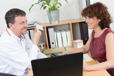 doctor holding pills: Cheerful male doctor holding pills in front of female rep Stock Photo