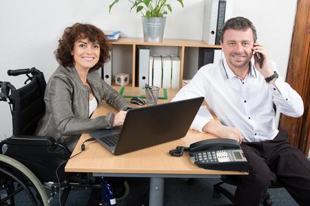 paraplegia: Man comforting a  woman in a wheelchair at work