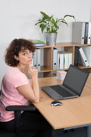 homeoffice: Middle-aged woman working on laptop at office Stock Photo