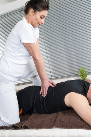 female therapist: Man getting massage in wooden spa. Female therapist.
