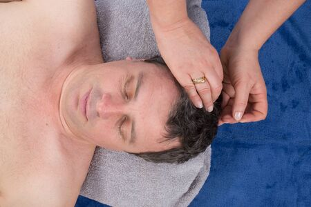 cranial: Man receiving cranial acupuncture, on health center Stock Photo