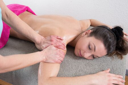 connective: Therapist doing a pressure point massage of deltoids muscle on a womans right shoulder