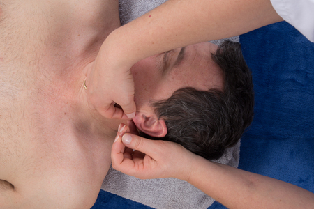 acupuncturist: Close-up of a  acupuncturist holding needle near ear