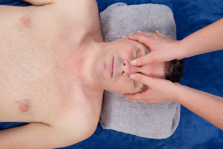 tuina: Bright woman receiving a face chinese massage in a spa center