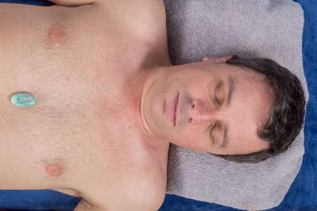 solar plexus: Alternative medicine, therapist using gemstones for lithotherapy - turquoise on solar plexus