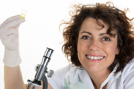 toiling: Curious research scientist in lab coat and rubber gloves looking at specimen under microscope in laboratory Stock Photo