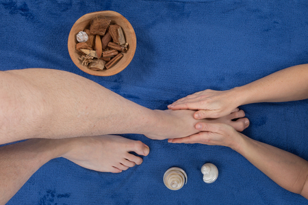 vertical wellness: Feet being massaged by female masseuse on white towel