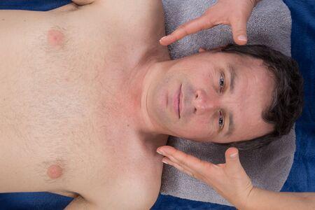 reiki: Peaceful man getting reiki treatment at the spa
