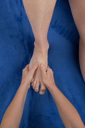 masseuse: Close up of female masseuse giving a foot massage to man