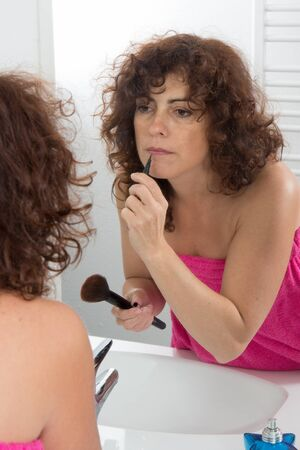 lip pencil: Middle-aged woman applying lip pencil and looking in mirror.