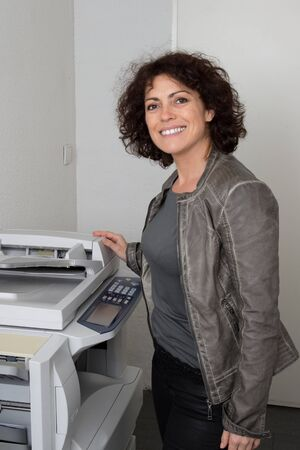 copy machine: Lovely and happy secretary using a copy machine at work