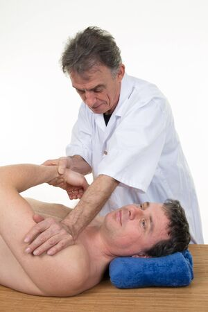 diagnosing: Physiotherapist diagnosing male patient after injury