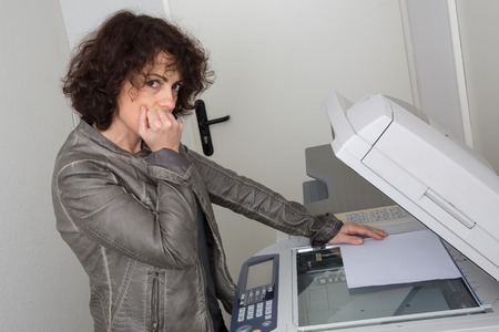 distressing: Business woman having trouble with copy machine Stock Photo