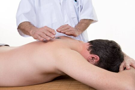 spirituality therapy: Male healer standing behind supine male client with hands isolated